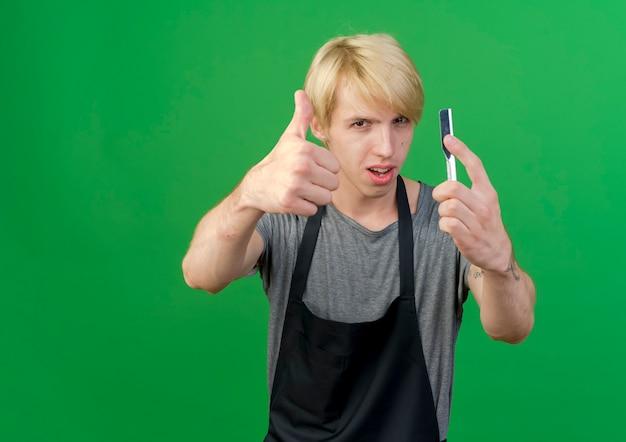 엄지 손가락을 보여주는 면도칼을 들고 앞치마에 전문 이발사 남자