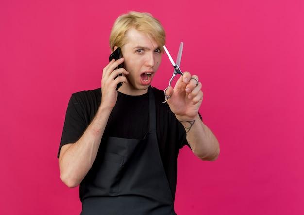 유쾌 하 게 웃 고 휴대 전화에 얘기 앞치마 들고 가위에 전문 이발사 남자