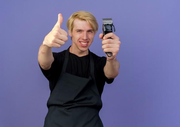 青い壁の上に立って親指を見せて幸せで陽気なトリマーを保持しているエプロンのプロの理髪店の男