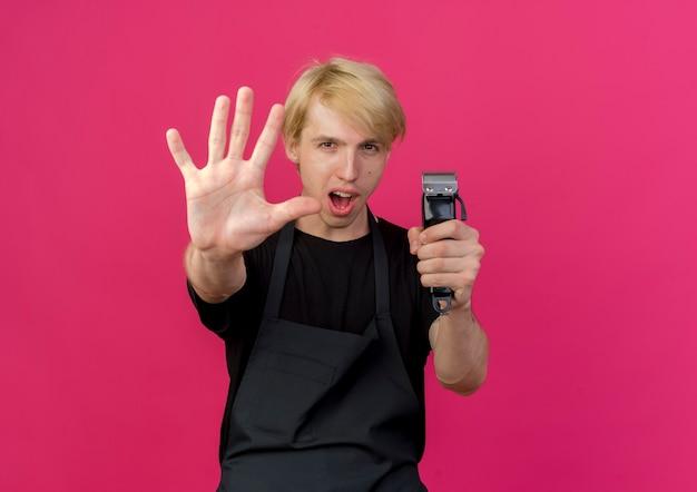 エプロンを持ったプロの理髪師がトリマーを持って指5番を見せて上向き