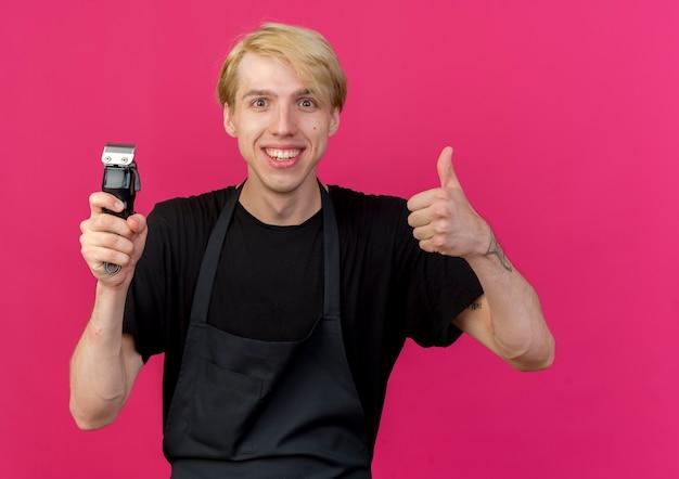 親指を上げて笑顔のトリマーを保持しているエプロンのプロの床屋の男