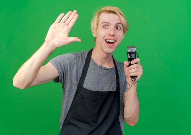 Профессиональный парикмахер в фартуке, держащий триммер, машет рукой, дружелюбно улыбаясь, стоя над зеленой стеной