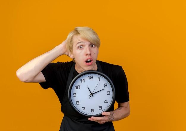 オレンジ色の壁の上に立っている彼の頭の上の手と混同されている正面を見て壁時計を保持しているエプロンのプロの理髪店の男