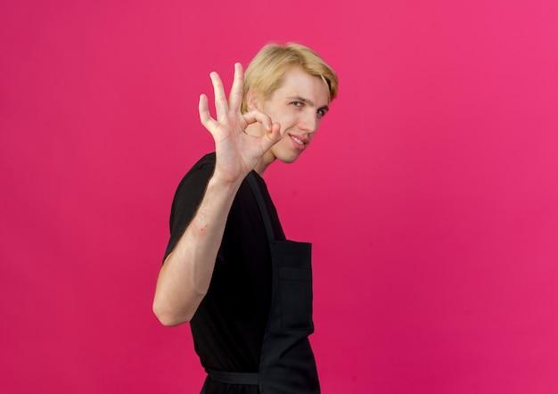 Профессиональный парикмахер в фартуке, глядя вперед, показывая знак ок, уверенно улыбаясь, стоя над розовой стеной
