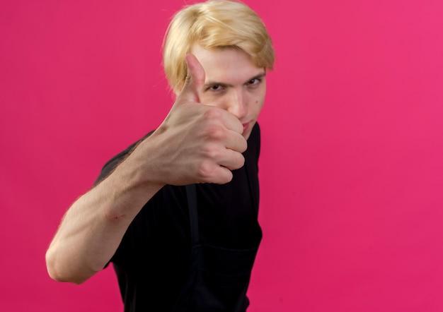 ピンクの壁の上に立って笑顔で親指を見せて正面を見てエプロンのプロの理髪店の男