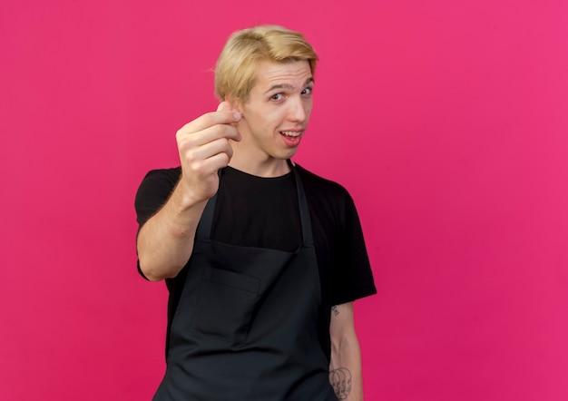 앞치마에 전문 이발사 남자가 분홍색 벽 위에 서있는 손가락을 문지르고 돈을 제스처를 웃고 웃고