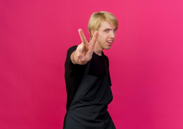 Профессиональный парикмахер в фартуке, глядя на переднюю улыбку, показывая v-знак, стоящий над розовой стеной