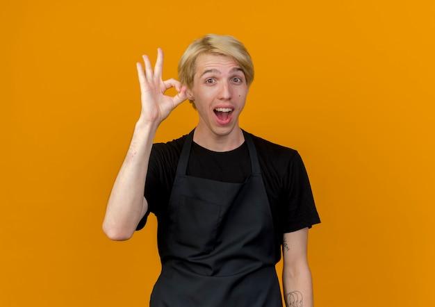 Профессиональный парикмахер в фартуке, глядя на переднюю улыбку, весело показывая знак ок, стоящий над оранжевой стеной