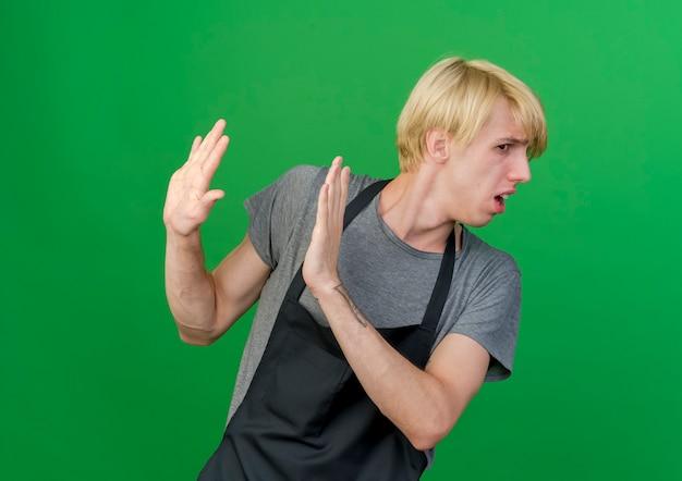 Профессиональный парикмахер в фартуке делает защитный жест испуганными руками