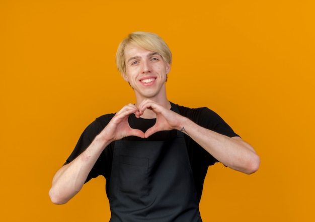 オレンジ色の壁の上に元気に幸せで前向きに立って笑顔の正面を指でハートジェスチャーを作るエプロンのプロの理髪店の男