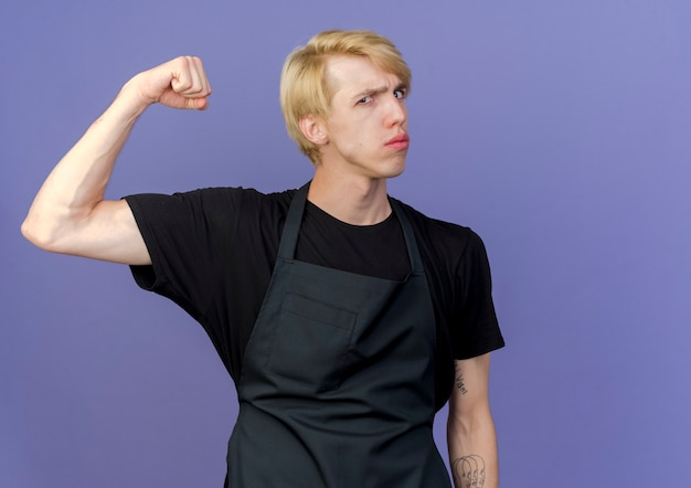 Профессиональный парикмахер в фартуке, поднимающий кулак, демонстрирующий бицепсы, уверенно выглядящий с серьезным выражением лица
