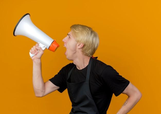 오렌지 벽 위에 큰 소리로 서 확성기를 외치는 앞치마에 전문 이발사 남자