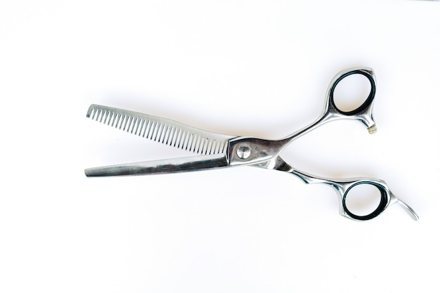 Инструменты для стрижки волос профессионального парикмахера на белом фоне.