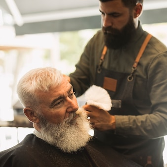 Professional barber with shave brush and old male client