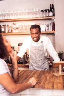 Профессиональный бариста. веселый позитивный мужчина смотрит на клиента, готовый принять заказ