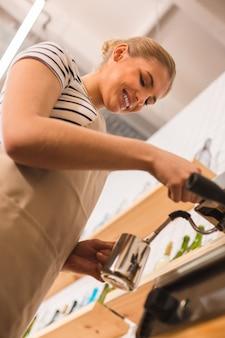 プロのバリスタ。コーヒーマシンの近くに立って、コーヒーを準備しながら笑顔で喜んでポジティブな素敵な女性