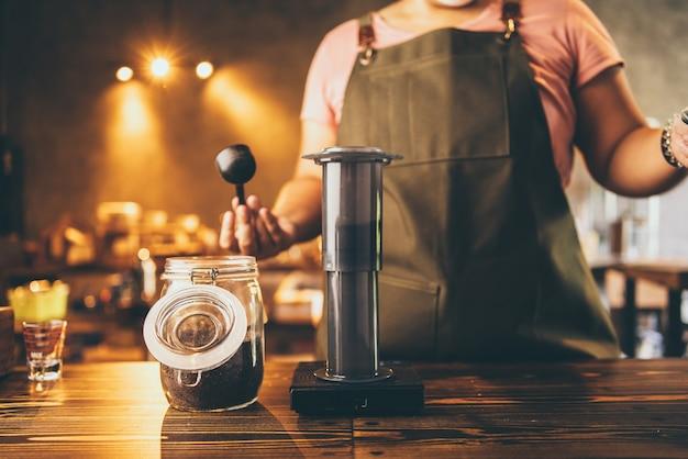 전문 바리스타는 컵에 차와 우유를 곁들인 신선한 음료를 만들고, 맛있는 바 카페, 커피숍이나 음식 레스토랑에서 우유 라떼를 손에 들고, 카페테리아 유니폼을 입고 일하는 바텐더