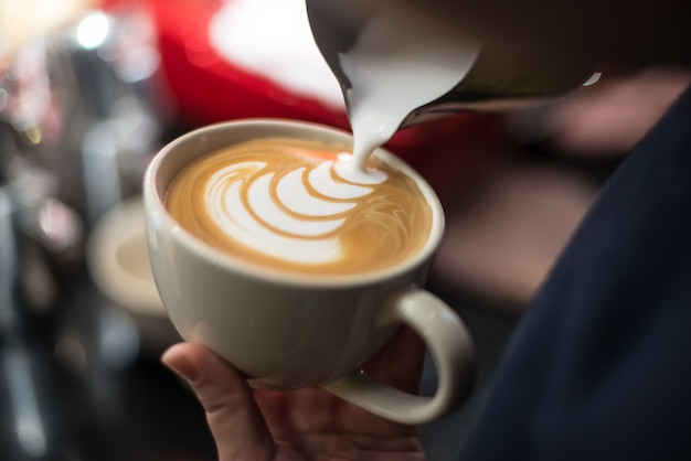 Professional barista pouring milk into the cup of coffee