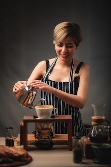 プロのバリスタがchemexを使用してコーヒーを準備し、淹れるとき、コーヒーメーカーとドリップケトルに注ぎます。コーヒーを作る若い女性