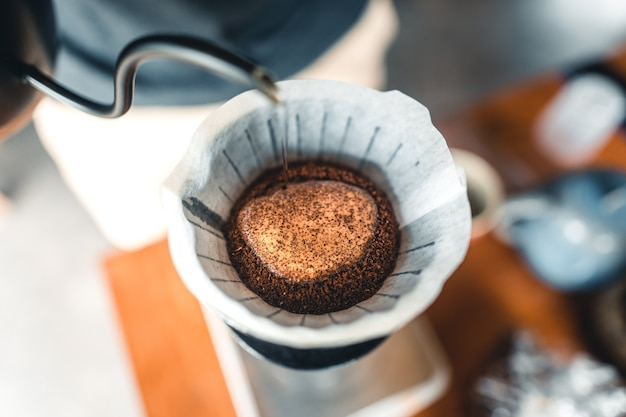 コーヒーメーカーとドリップケトルに注ぐコーヒーを準備するプロのバリスタ