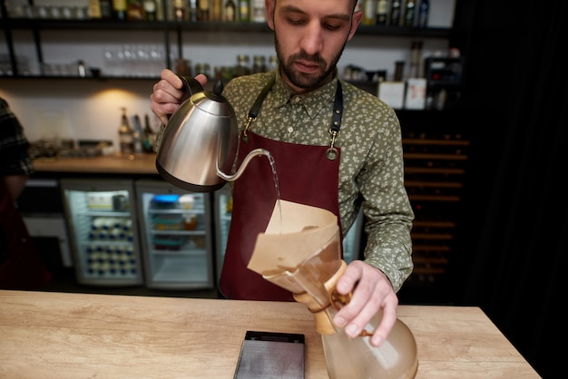 Professional barista preparing coffee using chemex pour over coffee maker and drip kettle. alternative ways of brewing coffee. coffee shop concept.