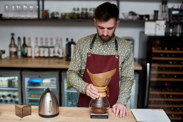 케미 넥스를 사용하여 커피를 준비하는 전문 바리 스타는 커피 메이커와 물 주전자 위에 붓습니다. 커피를 추출하는 다른 방법. 커피 숍 개념입니다.