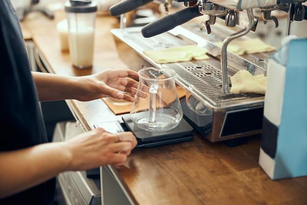 Chemex를 사용하여 커피를 준비하는 전문 바리 스타가 커피 메이커와 드립 케틀 위에 붓습니다.