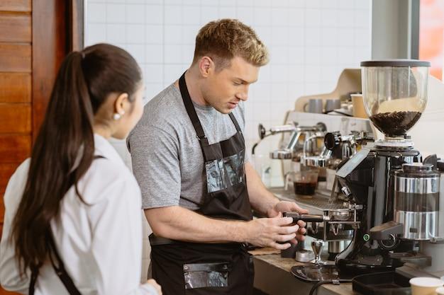 Профессиональный бариста, работающий в кафе, преподает приготовление кофе с помощью кофемашины эспрессо новым молодым сотрудникам.