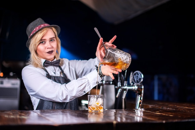 Профессиональная барменша готовит коктейль, стоя возле барной стойки в баре