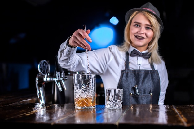 Professional barmaid places the finishing touches on a drink on the bar