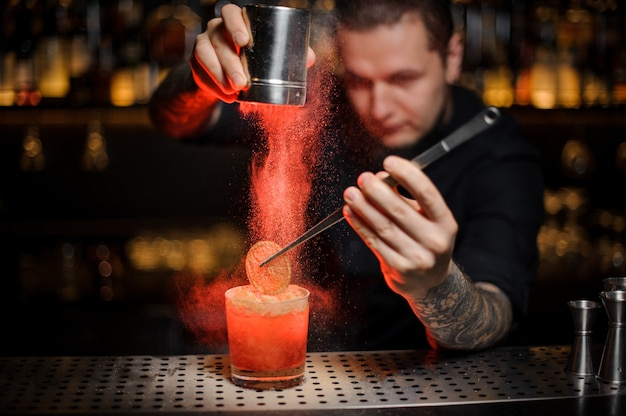 Professional barman adding to an alcoholic cocktail in the glass a dried orange with tweezers and aromatic powder in the red light on the bar counter.