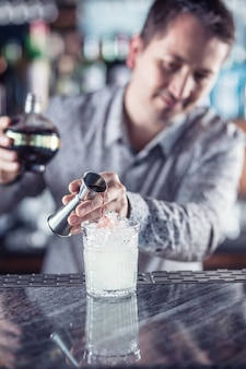 アルコールカクテルを作るプロのバーテンダー。