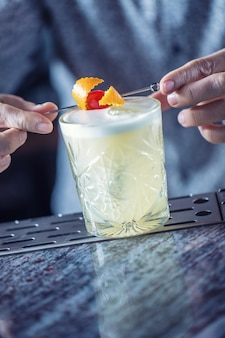 Professional barman making cocktail drink and decorated with fruits.
