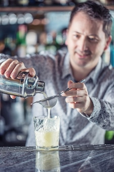 Professional barman making cocktail drink and pouring alcohol.