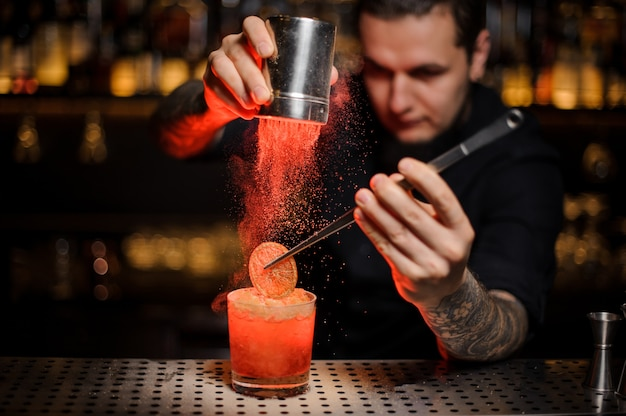 Professional bartender adding to an alcoholic cocktail in the glass a dried orange with tweezers and aromatic powder on the bar counter