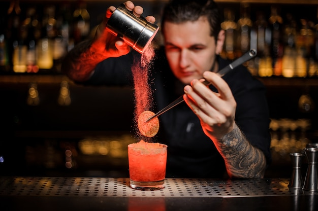 Professional bartender adding to an alcoholic cocktail in the glass a dried orange with tweezers and aromatic powder in the red light on the bar counter.