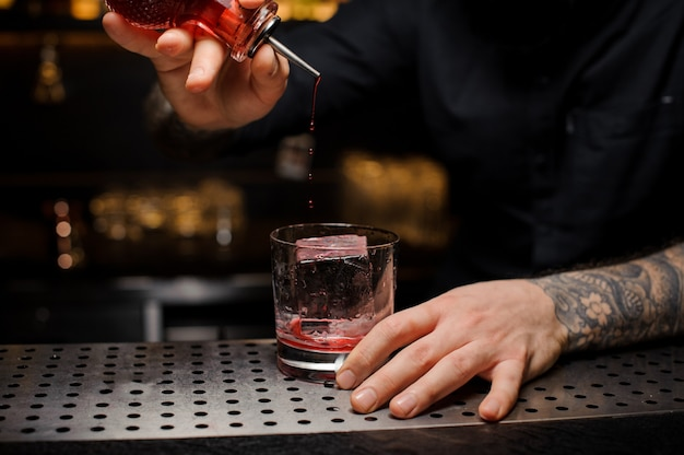 Professional bartender adding a bitter to the delicious cocktail from the special dasher bottle on the bar counter
