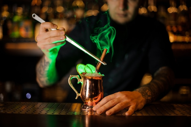 Professional bartender adding to a cocktail in the cooper glass with a dried orange aromatic smoked cinnamon with tweezers on the bar counter