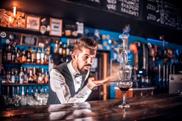 Professional bartender intensely finishes his creation in cocktail bars