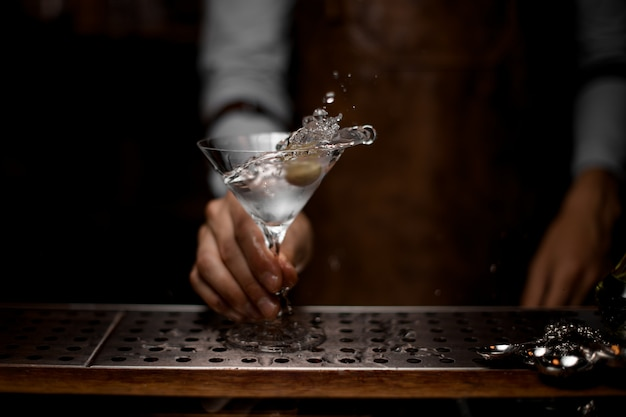Professional bartender mixing a transparent alcoholic drink in the martini glass with one olive