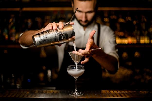 Профессиональный бармен наливает белый коктейль из стального шейкера в стакан через сито