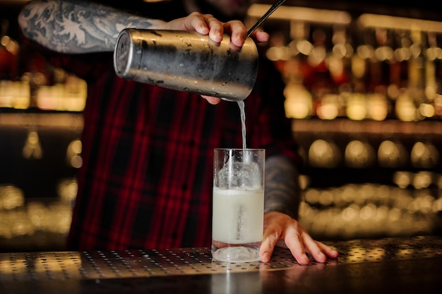 Professional bartender pouring a gin fizz cocktail from the steel shaker to a glass on the bar counter