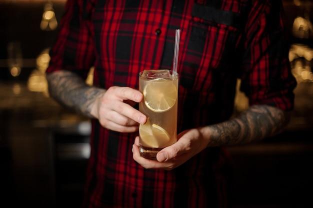 바 카운터에 얼음 조각과 오렌지가 들어간 레모네이드 칵테일 한 잔을 제공하는 전문 바텐더