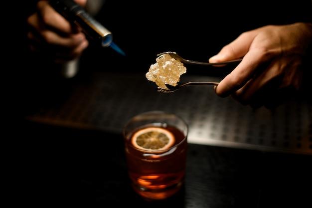 Professional bartender serving a brown cocktail melting caramel with a burner above the lemon slice