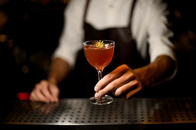 Professional bartender serving a cocktail in the glass with a little yellow flower