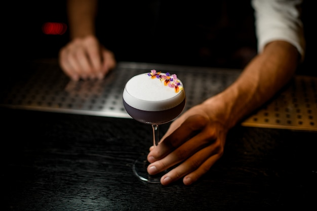 Professional bartender serving a cocktail with white scum decorated with flower petals on the bar counter