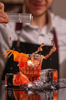 Профессиональный бармен бросает в красный бокал для коктейля стоя на барной стойке кубик льда с всплеск