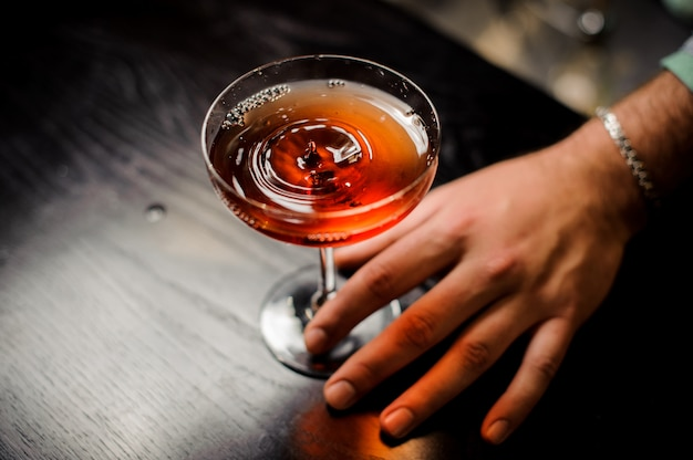 Professional bartender with red cocktail