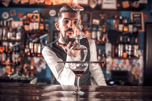 Профессиональный бармен украшает красочную смесь, стоя у барной стойки в пабе