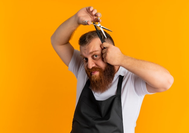 Professional bearded barber man in apron cutting his hair with scissors standing over orange wall